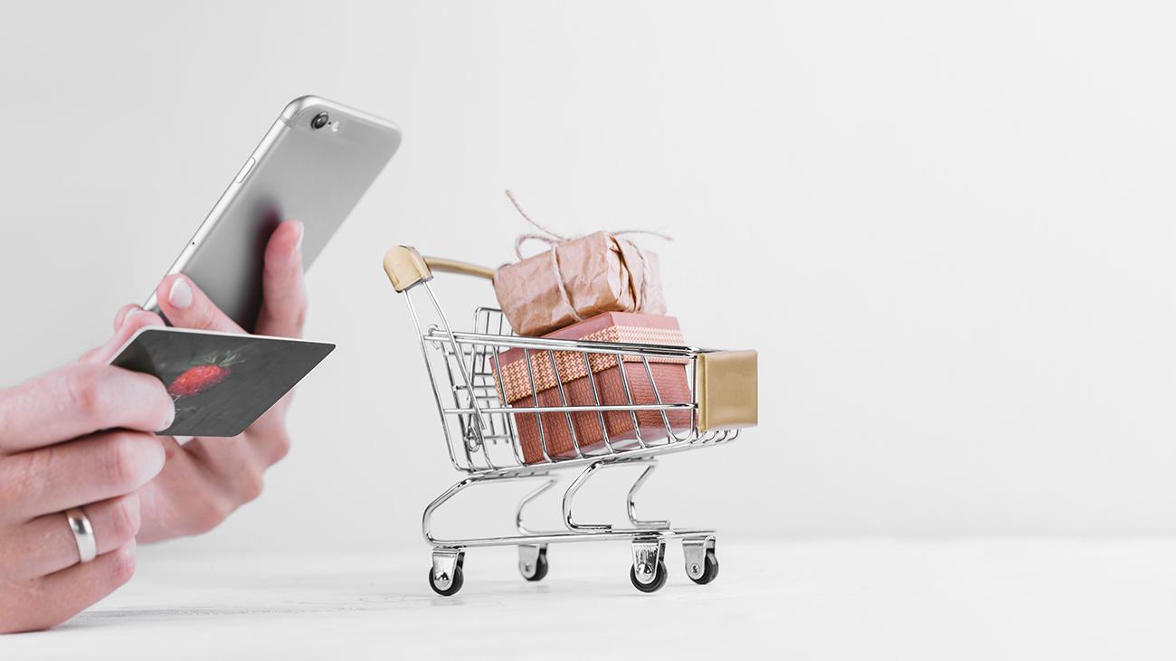 Gift card como canal de vendas: mão de mulher segurando celular e cartão
