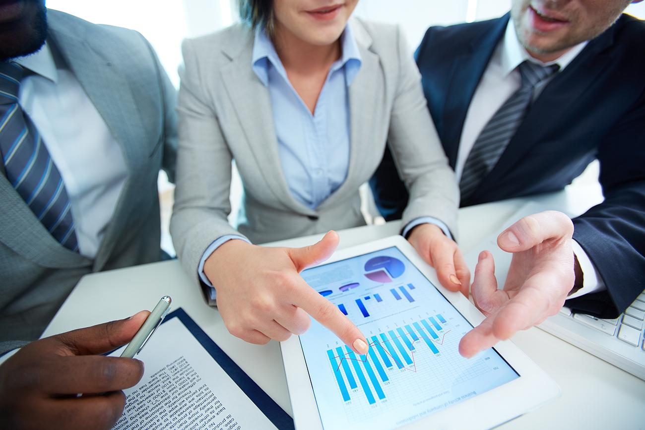 Colegas de trabalho analisando gráfico em dispositivo móvel e planejando como aumentar as vendas