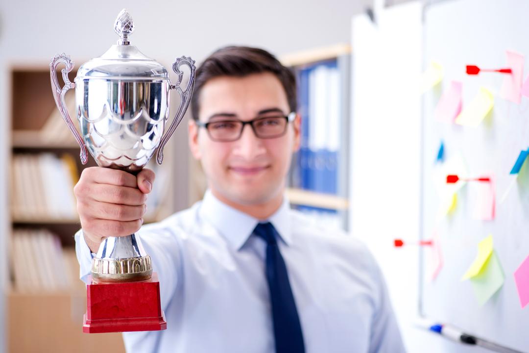 Motivar funcionários: jovem recebendo segurando troféu no trabalho
