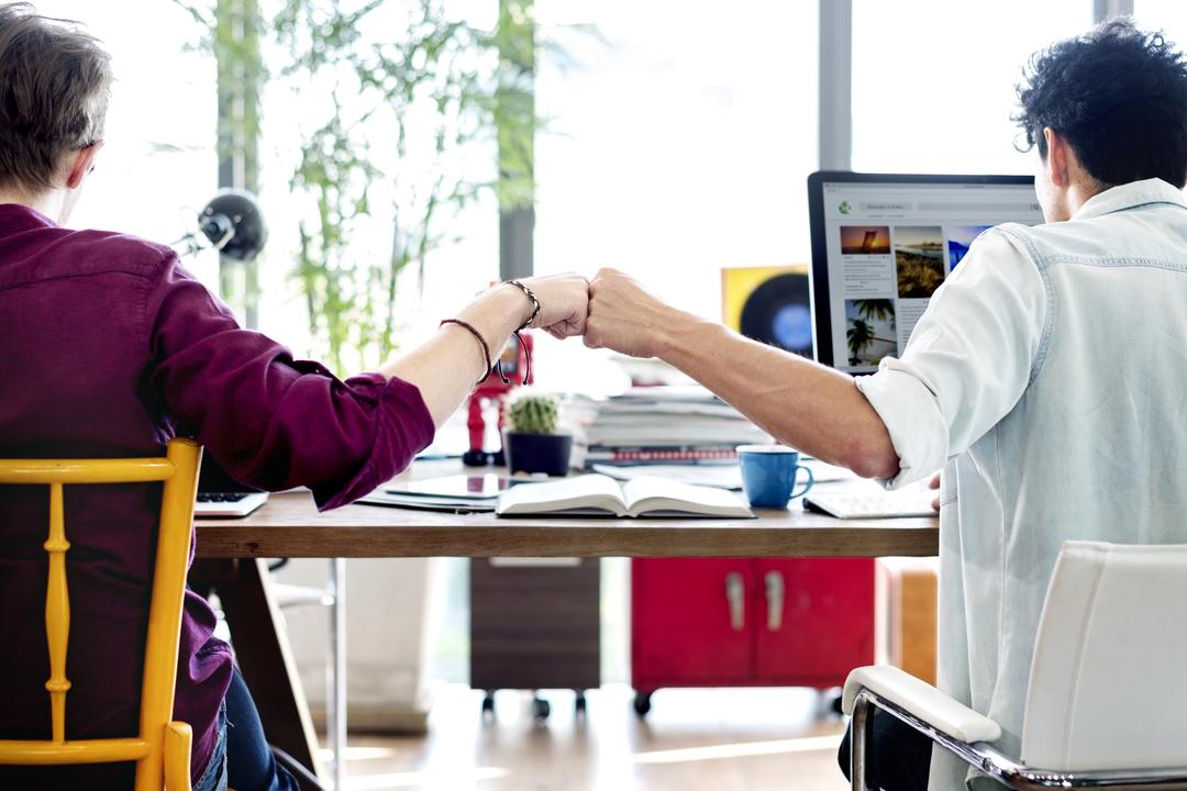 Marketing de relacionamento: amigos sentado lado a lado batendo os punhos como um trabalho em equipe