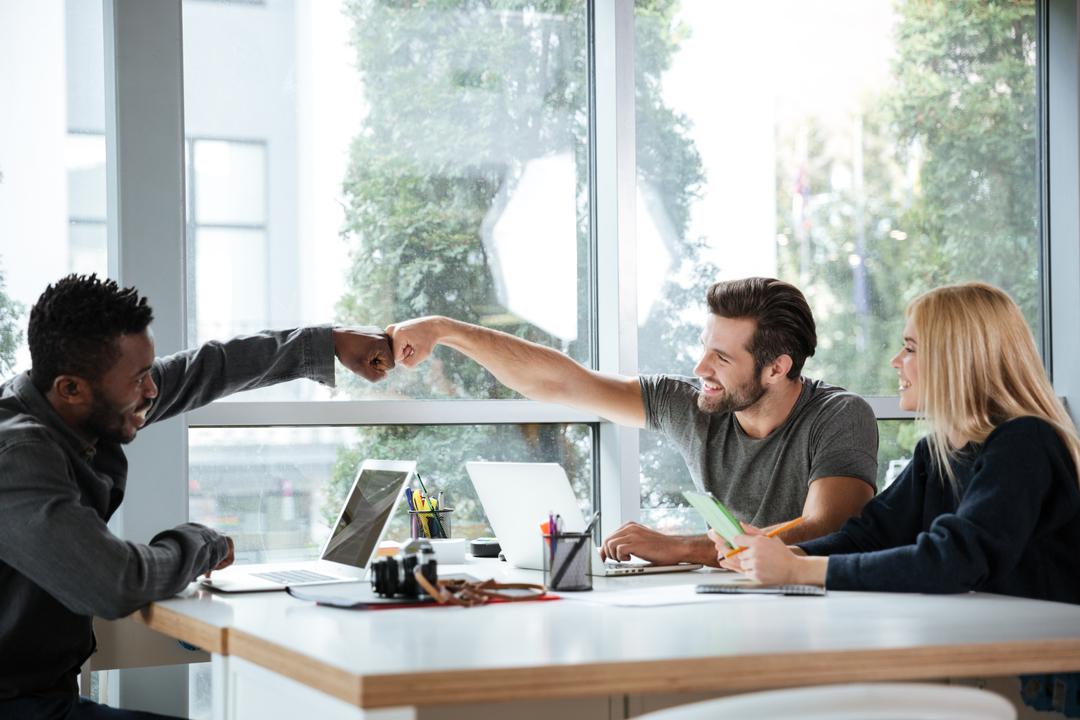 Como melhorar o clima organizacional: colegas de trabalho sorrindo sentados à mesa