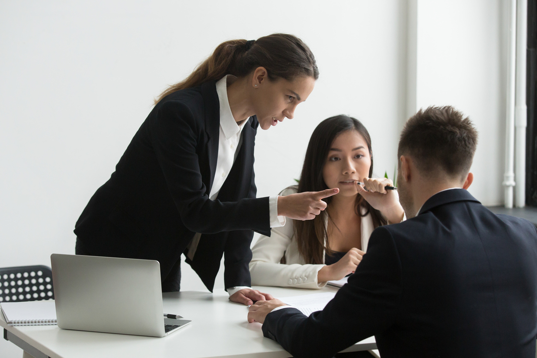 Funcionários desmotivados: mulher executiva apontando dedo para funcionário homem