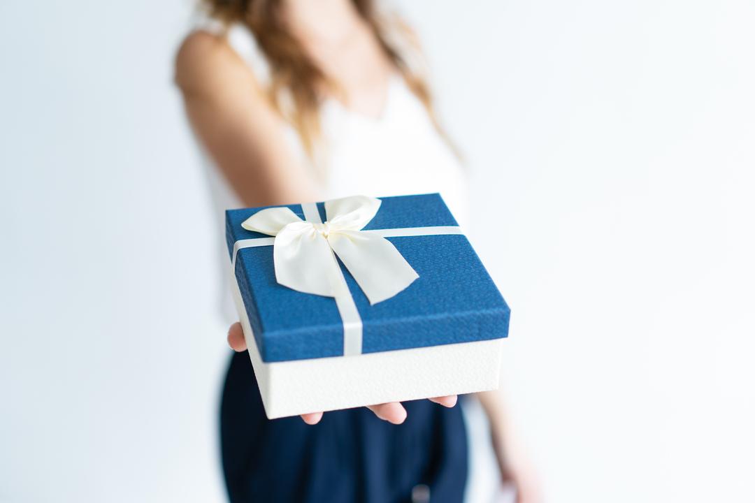 Premiação de funcionários: mulher segurando caixa de presente na palma da mão