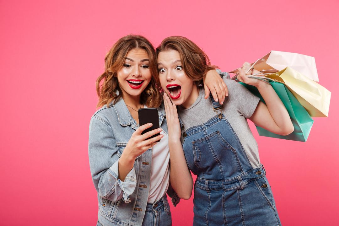 Duas amigas vendo lojas divulgar produtos em promoção e com opção de aceitar gift cards