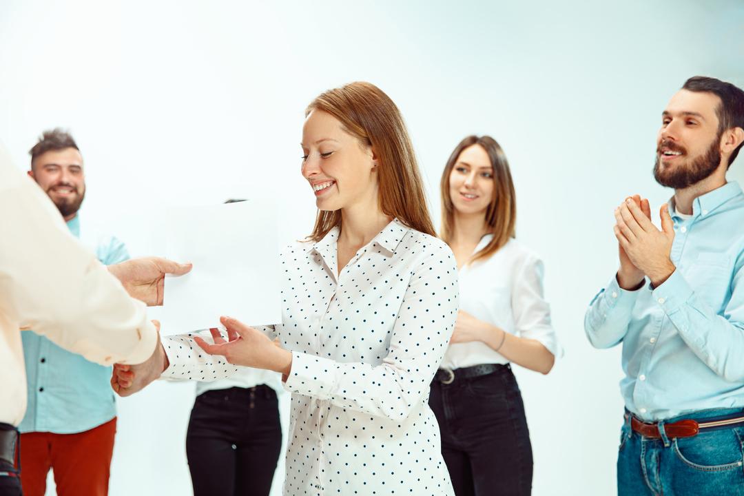 Funcionária recebendo benefícios empresariais oferecidos pela empresa e sendo parabenizada pelos colegas de trabalho