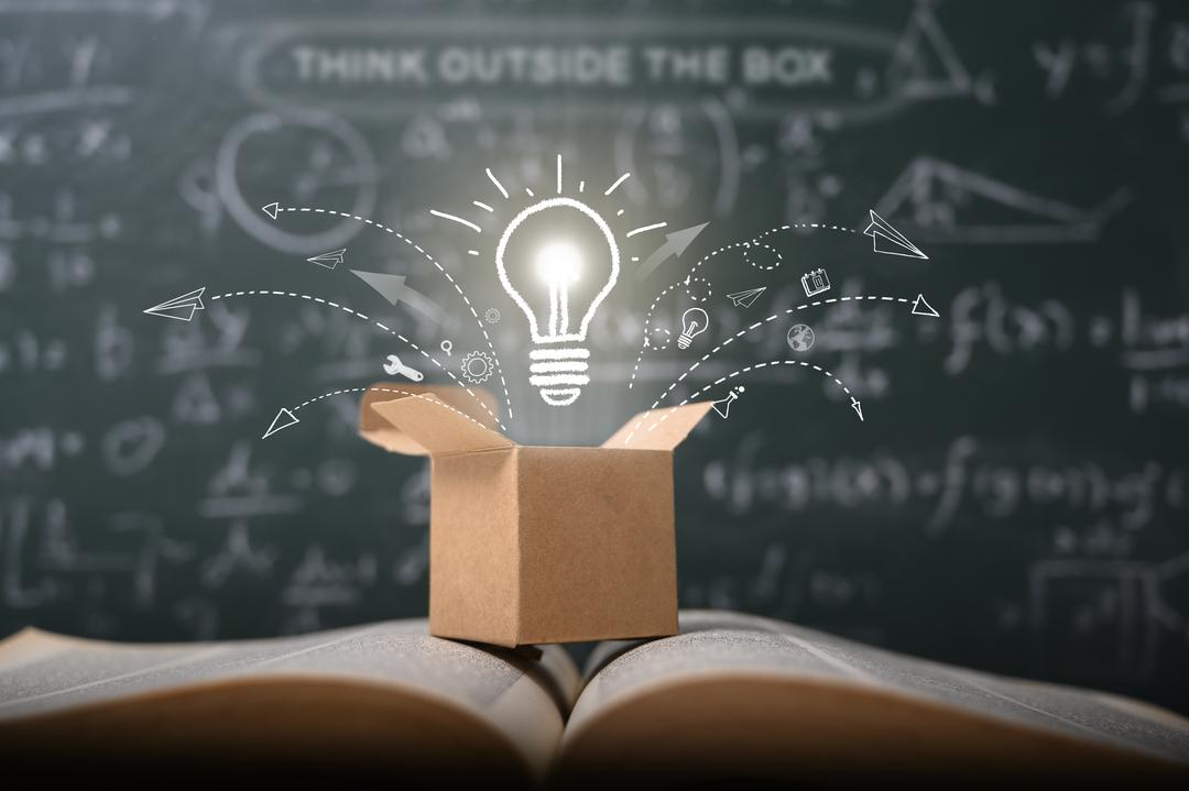 Uma lâmpada acesa em cima de um livro aberto simbolizando uma forma de como inovar nas vendas