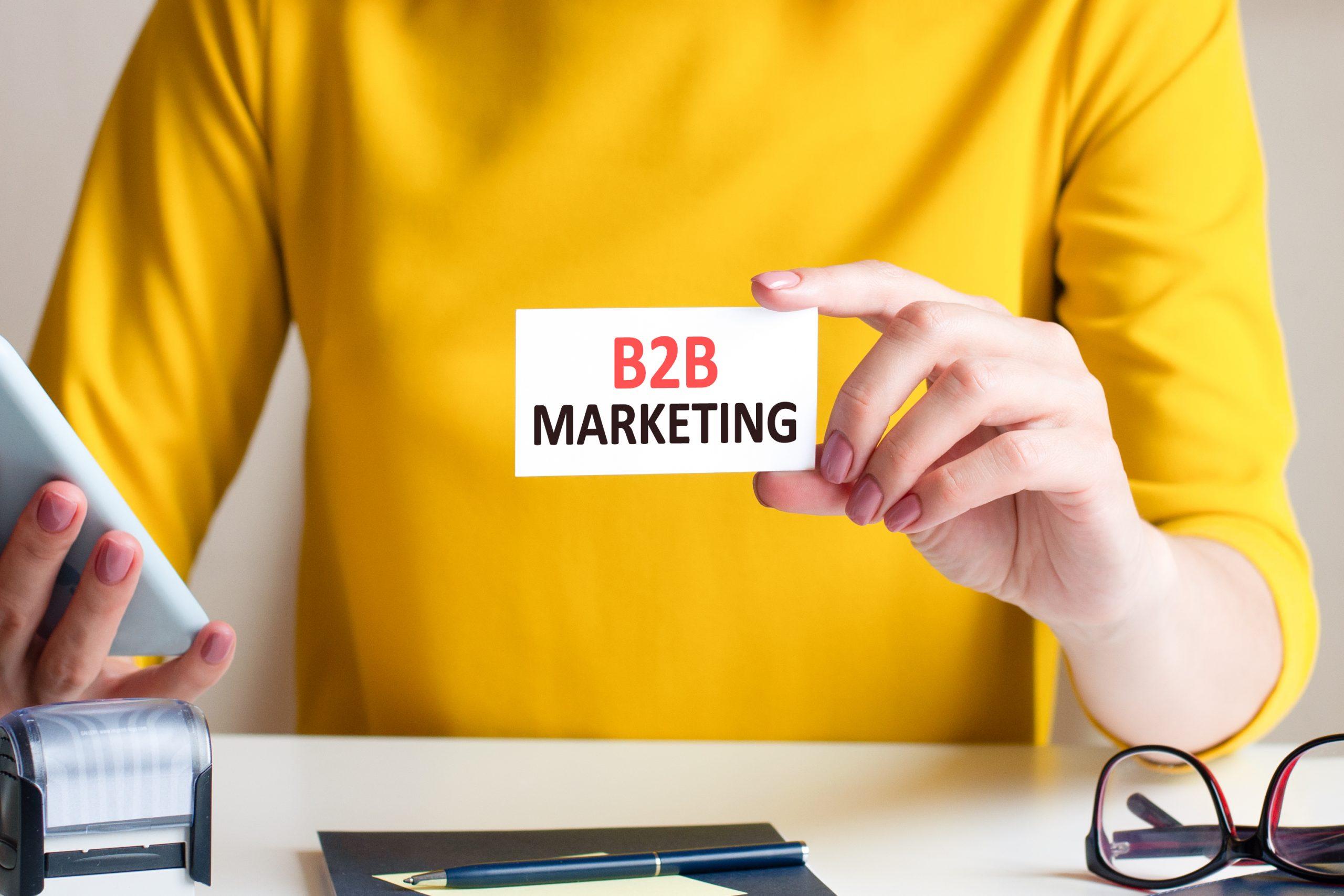 Uma pessoa com camisa amarela segurando um pequeno cartão escrito marketing B2B